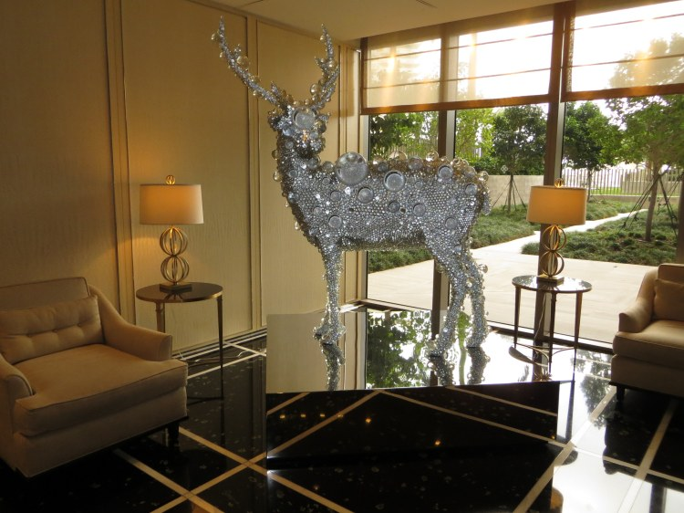 A deer sculpture covered in crystal beads stands at the corner of the reception area