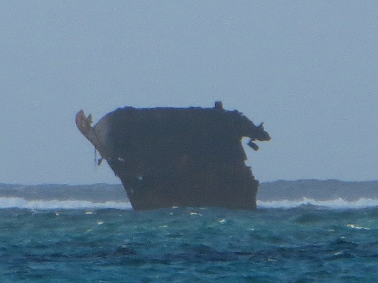 There is a wrecked freighter ship just off the shore.