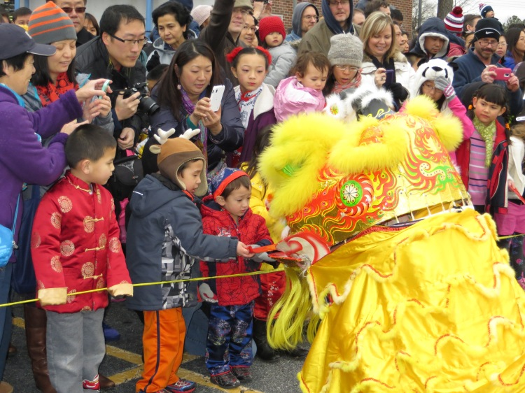 Children offering money-filled red envelops to the Lion