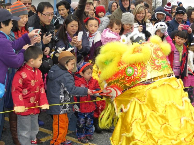 Children offering money-filled red envelops to the Lion