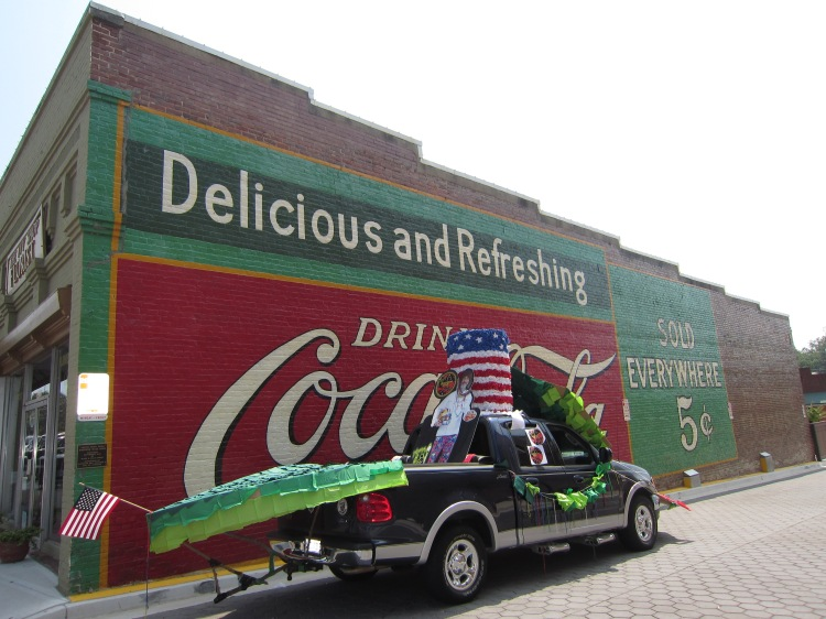 Chef Henry's truck parked in front of a restored Coca Cola mural in downtown Acworth